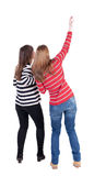 Two long haired friendly women pointing . Stock Photography