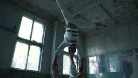 Two loony men doing acrobatic exercises and headstand on leg in hall in slo-mo. Striking view of two young kook men in white uniforms doing acrobatic exercises stock footage