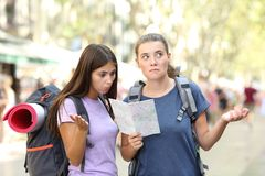 Two lost backpackers trying to find location. Consulting a paper guide in the street stock images