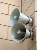 Two loudspeakers. Two speakers are installed on a wall of a building Stock Photos