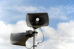 Loudspeakers. Two loudspeakers attached to pole. Cloudy sky on background. Clipping path included, making isolation easy Stock Photos