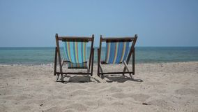 Two lounge chairs on the beach. Two lounge chairs on a beach stock video