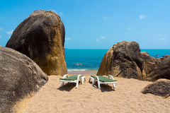 Two lounge chairs on the beach Stock Images