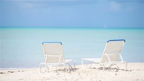 Two lounge chairs on beautiful tropical beach at Maldives. White lounge chairs on beautiful tropical beach at Maldives stock video footage