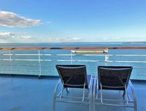 Two lounge chairs on a cruise ship deck overlooking the ocean and a beautiful blue sky. Two lounge chairs on a cruise ship deck with views of the ocean and a royalty free stock photos