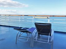 Two lounge chairs on a cruise ship deck overlooking the ocean and a beautiful blue sky. Two lounge chairs on a cruise ship deck with views of the ocean and a royalty free stock images