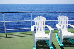 Two lounge chairs on the deck of pleasure boat. Sea trip in a sunny summer day stock images