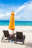 Two lounge chairs with sun umbrella Stock Images