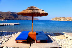Two lounge chairs with sun umbrella on a beach, Greece Royalty Free Stock Image