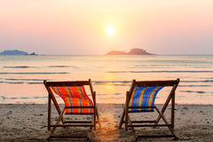 Two lounge chairs on sunset beach. Relax. Stock Photos