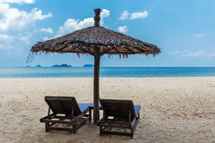 Two lounge chairs and a sunshade umbrella on the beach Royalty Free Stock Photos
