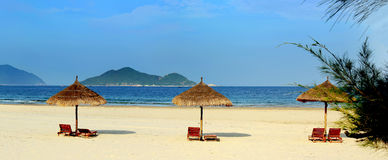 Two lounge chairs thatched umbrella on beach Stock Photo