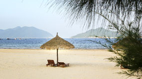 Two lounge chairs thatched umbrella on beach royalty free stock photo