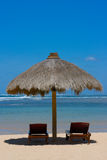 Two lounge chairs under tent on beach. Two lounge chairs under awning on beach Stock Photo