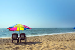 Two lounge chairs under an umbrella on the beach Royalty Free Stock Images
