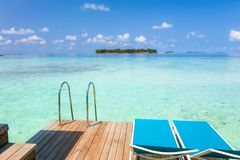 Two lounge chairs on the wooden deck with Maldives turquoise wa. Ter sea view for summer vacations holiday concept stock photography