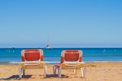 Two loungers on the beach are turned towards the sea. With a yachts royalty free stock photo