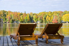 Two Loungers on a Boardwalk by a Lake in the Fall Royalty Free Stock Photos