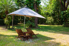 Two loungers parasol on a lawn at the garden Stock Photo