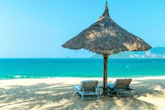 Two loungers under strawy parasol on sandy beach. For relax stock photo