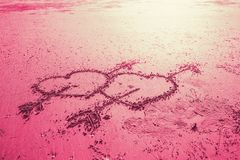 Pink two love heart sign with cupid arrow hand draw on the beach. Two love heart sign with cupid arrow hand draw on the beach pink sweet color tone Stock Photography