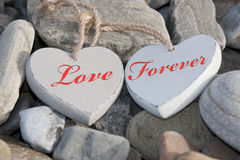 Two love hearts on a rocky beach as one Stock Photos