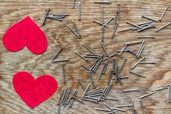 Two red hearts on wooden background surrounded by iron nails. Two love hearts on wooden background surrounded by iron nails stock photos