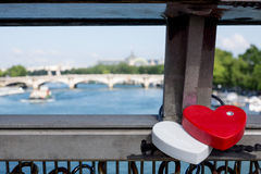 Two love locks on Paris bridge. Red and White pair of love locks on Paris bridge with view to other bridges Stock Image
