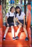 Two lovely asian teeenager relaxing in children play ground stock photos