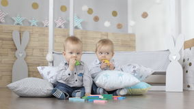 Two lovely baby twins are building houses of  colorful cubes. And toy blocks stock footage