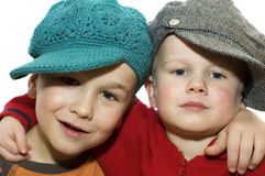 Two lovely brothers -2. Two lovely brothers wit hats, holding each other royalty free stock photo