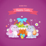 Two lovely festive rabbits, near the basket with Easter eggs. Royalty Free Stock Images