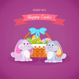 Two lovely festive rabbits, near the basket with Easter eggs. Royalty Free Stock Photos