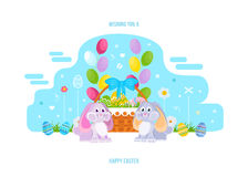 Two lovely festive rabbits, near the basket with Easter eggs. Stock Photo