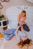Two lovely funny sisters having much fun on queen size bed. Queen size bed. Two lovely funny sisters wearing pajamas having much fun on queen size bed stock photography
