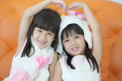 Two lovely girl use hand cover and touch to make heart sign toge Royalty Free Stock Image