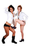 Two lovely girls. Two young woman in bikini and white blouse and black boots standing Stock Photography