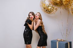 Two lovely girls in similar black dresses posing with kissing face expression at birthday party. Long-haired european. Lady standing beside balloons and gifts stock photo
