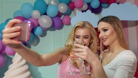 Two girls with glasses of champagne take a selfie. Two lovely happy girls with glasses of champagne in their hands take a selfie in the room decorated with huge stock video