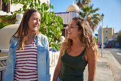 Two lovely laughing young girls enjoying. Two lovely young girls out for a stroll looking at each other and laughing happily while enjoying to be outside in the Royalty Free Stock Images