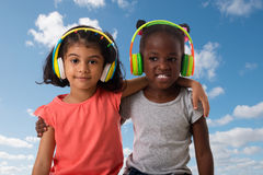 Two lovely little girls with headphones. Royalty Free Stock Photos