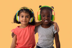 Two lovely little girls with headphones. Music and technology concept.Two lovely happy little girls with headphones on yellow background royalty free stock photo