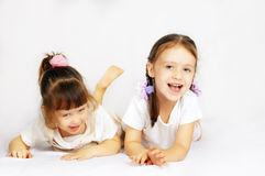 Two lovely little girls playing on the floor Stock Photo