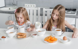 Two lovely sisters eating healthy breakfast Royalty Free Stock Photography