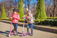Two lovely sisters ride scooters on a warm sunny spring day Royalty Free Stock Photos