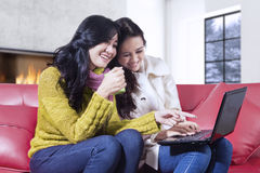 Two lovely women using laptop at home Royalty Free Stock Photography