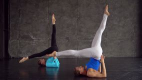Two lovely yoga women doing yoga together in studio with large windows. Women doing a yoga class. Couple does yoga stock footage