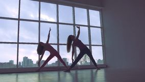 Two lovely yoga women doing yoga together in studio with large windows. Two lovely yoga women doing yoga together in home with large windows stock footage