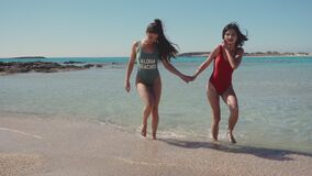Two lovely young lesbian girls on the beach. Lesbian, lgbt, gay, friendship, travel, relationship concept. Lifestyle