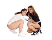 Two lovely young woman crouching. Two woman, Caucasian and East Indian, crouching on the floor Royalty Free Stock Image